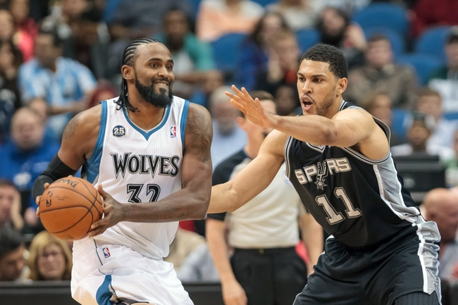 Apr 8, 2014; Minneapolis, MN, USA; Minnesota Timberwolves center Ronny Turiaf (32) passes in the fourth quarter against the San Antonio Spurs center Jeff Ayres (11) at Target Center. The Minnesota Timberwolves win 110-91. Mandatory Credit: Brad Rempel-USA TODAY Sports