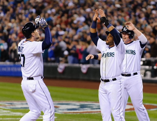 Apr 8, 2014; Seattle, WA, USA; Seattle Mariners second baseman Robinson Cano (22) and Seattle Mariners first baseman Justin Smoak (17) celebrate with Seattle Mariners designated hitter Corey Hart (27) at home plate after Hart hit a three-run home run against the Los Angeles Angels during the third inning at Safeco Field. Mandatory Credit: Steven Bisig-USA TODAY Sports