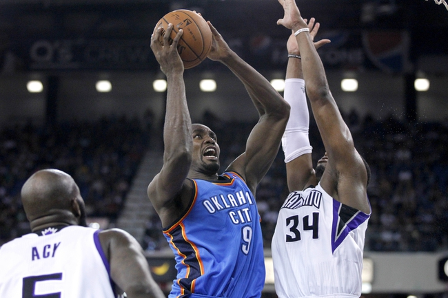 Apr 8, 2014; Sacramento, CA, USA; Oklahoma City Thunder forward Serge Ibaka (9) attempts a shot over Sacramento Kings forward Jason Thompson (34) in the second quarter at Sleep Train Arena. Mandatory Credit: Cary Edmondson-USA TODAY Sports