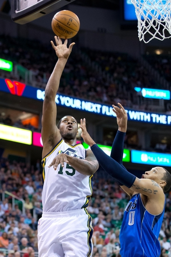 Apr 8, 2014; Salt Lake City, UT, USA; Utah Jazz center Derrick Favors (15) shoots over Dallas Mavericks forward Shawn Marion (0) during the second half at EnergySolutions Arena. The Mavericks won 95-83. Mandatory Credit: Russ Isabella-USA TODAY Sports