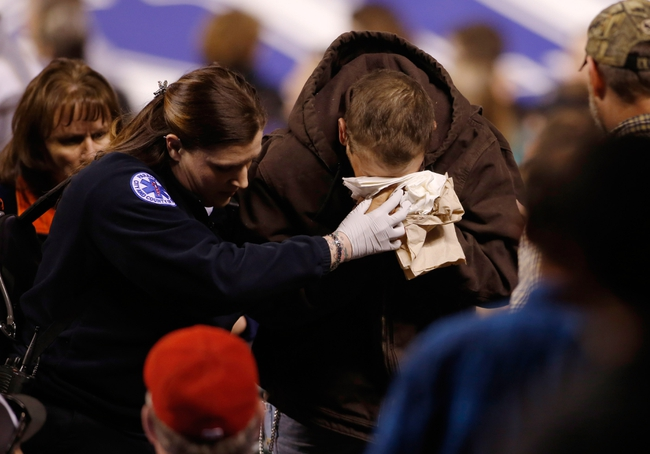 Apr 8, 2014; Denver, CO, USA; A fan is helped out of the stands by a paramedic after being hit by a baseball during the eighth inning between the Colorado Rockies and the Chicago White Sox at Coors Field.  The White Sox won 15-3.  Mandatory Credit: Chris Humphreys-USA TODAY Sports
