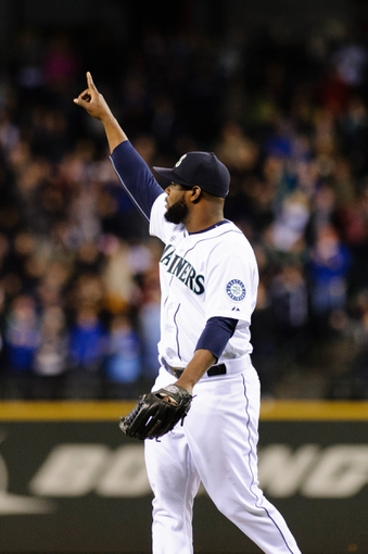 Apr 8, 2014; Seattle, WA, USA; Seattle Mariners closing pitcher Fernando Rodney (56) points to the ball for the final out of the game against the Los Angeles Angels at Safeco Field.  Seattle defeated Los Angeles 5-3. Mandatory Credit: Steven Bisig-USA TODAY Sports