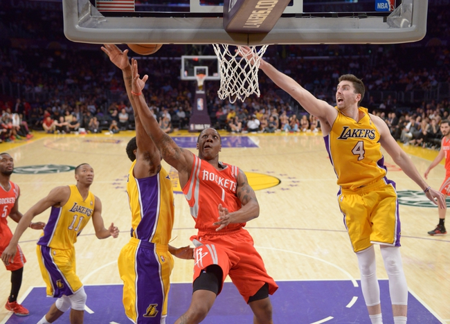 Apr 8, 2014; Los Angeles, CA, USA; Houston Rockets guard Isiah Canaan (1) is defended by Los Angeles Lakers guard MarShon Brooks (2) and forward Ryan Kelly (4) at Staples Center. Mandatory Credit: Kirby Lee-USA TODAY Sports