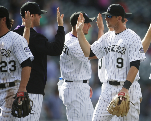 Apr 9, 2014; Denver, CO, USA;  Colorado Rockies second baseman DJ LeMahieu (9) celebrates with teammates after the defeating the Chicago White Sox 10-4 at Coors Field. Mandatory Credit: Chris Humphreys-USA TODAY Sports