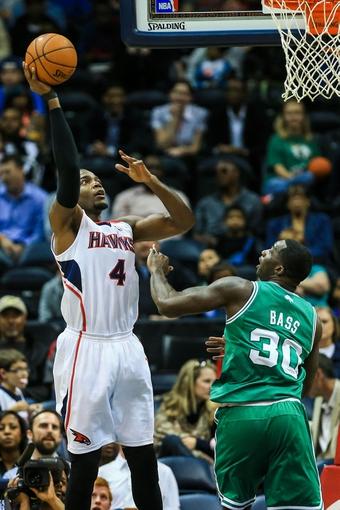 Apr 9, 2014; Atlanta, GA, USA; Atlanta Hawks forward Paul Millsap (4) shoots a basket over Boston Celtics forward Brandon Bass (30) in the first quarter at Philips Arena. Mandatory Credit: Daniel Shirey-USA TODAY Sports