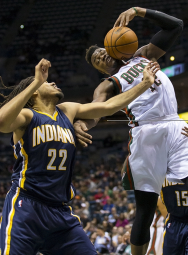 Apr 9, 2014; Milwaukee, WI, USA; Milwaukee Bucks forward Jeff Adrien (12) grabs a rebound as Indiana Pacers forward Chris Copeland (22) looks on during the second quarter at BMO Harris Bradley Center. Mandatory Credit: Jeff Hanisch-USA TODAY Sports