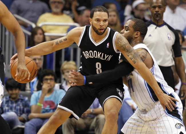 Apr 9, 2014; Orlando, FL, USA; Orlando Magic guard Jameer Nelson (14) fouls Brooklyn Nets guard Deron Williams (8) during the second half at Amway Center. Orlando Magic defeated the Brooklyn Nets 115-111. Mandatory Credit: Kim Klement-USA TODAY Sports