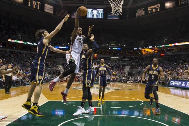 Apr 9, 2014; Milwaukee, WI, USA; Milwaukee Bucks forward Khris Middleton (22) shoots the ball as Indiana Pacers forward Luis Scola (4) defends during the third quarter at BMO Harris Bradley Center. Mandatory Credit: Jeff Hanisch-USA TODAY Sports