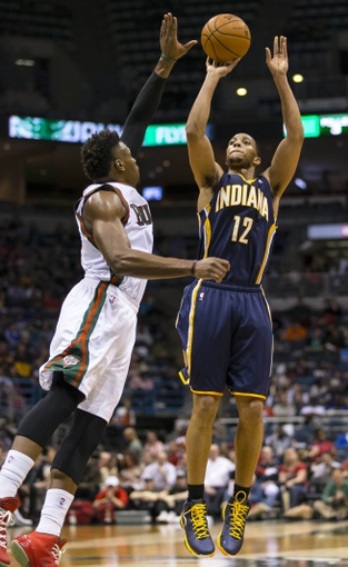 Apr 9, 2014; Milwaukee, WI, USA; Indiana Pacers forward Evan Turner (12) shoots the ball as Milwaukee Bucks forward Jeff Adrien (12) defends during the third quarter at BMO Harris Bradley Center. Mandatory Credit: Jeff Hanisch-USA TODAY Sports