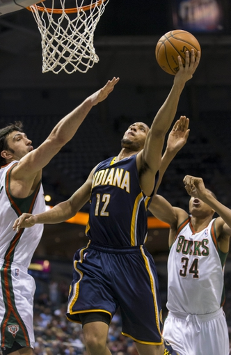 Apr 9, 2014; Milwaukee, WI, USA; Indiana Pacers forward Evan Turner (12) shoots the ball in front of Milwaukee Bucks center Zaza Pachulia (27) during the third quarter at BMO Harris Bradley Center. Mandatory Credit: Jeff Hanisch-USA TODAY Sports