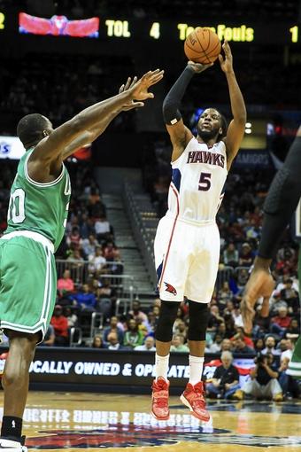 Apr 9, 2014; Atlanta, GA, USA; Atlanta Hawks forward DeMarre Carroll (5) shoots over Boston Celtics forward Brandon Bass (30) in the second half at Philips Arena. The Hawks won 105-97. Mandatory Credit: Daniel Shirey-USA TODAY Sports