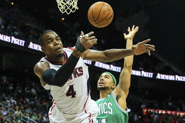 Apr 9, 2014; Atlanta, GA, USA; Atlanta Hawks forward Paul Millsap (4) is fouled on a shot attempt by Boston Celtics guard Jerryd Bayless (11) in the second half at Philips Arena. The Hawks won 105-97. Mandatory Credit: Daniel Shirey-USA TODAY Sports