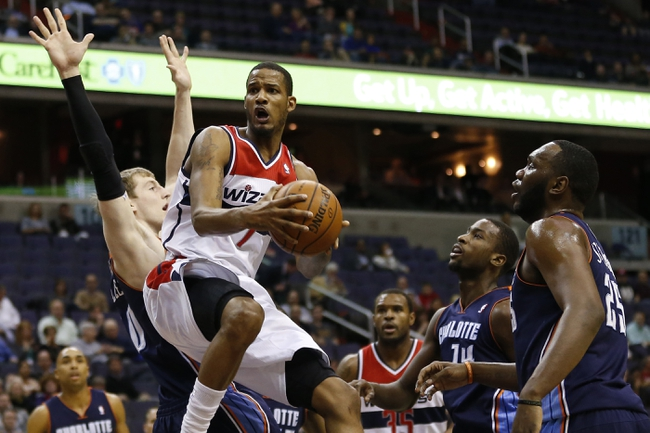 Apr 9, 2014; Washington, DC, USA; Washington Wizards forward Trevor Ariza (1) prepares to shoot the ball as Charlotte Bobcats center Cody Zeller (40) defends in the first quarter at Verizon Center. The Bobcats won 94-88 in overtime. Mandatory Credit: Geoff Burke-USA TODAY Sports