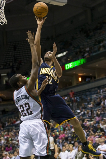 Apr 9, 2014; Milwaukee, WI, USA; Indiana Pacers forward Evan Turner (12) shoots the ball over Milwaukee Bucks forward Khris Middleton (22) during the fourth quarter at BMO Harris Bradley Center.  The Pacers won 104-102.  Mandatory Credit: Jeff Hanisch-USA TODAY Sports
