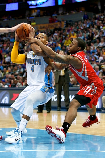 Apr 9, 2014; Denver, CO, USA; Houston Rockets point guard Isaiah Canaan (1) fouls Denver Nuggets point guard Randy Foye (4) in the third quarter at the Pepsi Center. The Nuggets won 123-116. Mandatory Credit: Isaiah J. Downing-USA TODAY Sports