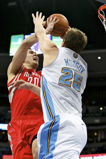 Apr 9, 2014; Denver, CO, USA; Denver Nuggets center Timofey Mozgov (25) blocks the shot of Houston Rockets power forward Donatas Motiejunas (20) in the first quarter at the Pepsi Center. Mandatory Credit: Isaiah J. Downing-USA TODAY Sports