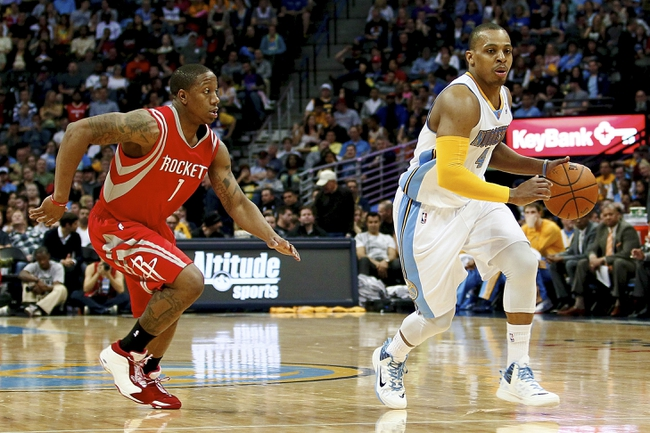 Apr 9, 2014; Denver, CO, USA; Denver Nuggets point guard Randy Foye (4) keeps the ball from Houston Rockets point guard Isaiah Canaan (1) in the fourth quarter at the Pepsi Center. The Nuggets won 123-116. Mandatory Credit: Isaiah J. Downing-USA TODAY Sports