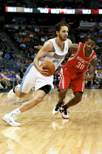 Apr 9, 2014; Denver, CO, USA; Denver Nuggets shooting guard Evan Fournier (94) dribbles the ball against Houston Rockets shooting guard Troy Daniels (30) in the fourth quarter at the Pepsi Center. The Nuggets won 123-116. Mandatory Credit: Isaiah J. Downing-USA TODAY Sports