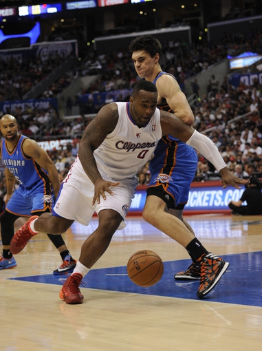 Apr 9, 2014; Los Angeles, CA, USA; Los Angeles Clippers forward Glen Davis (0) dribbles the ball as Oklahoma City Thunder center Steven Adams (R) defends during the fourth quarter at Staples Center. The Thunder won 107-101. Mandatory Credit: Kelvin Kuo-USA TODAY Sports