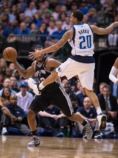 Apr 10, 2014; Dallas, TX, USA; San Antonio Spurs forward Kawhi Leonard (2) passes the ball by Dallas Mavericks guard Devin Harris (20) during the second half at the American Airlines Center. The Spurs defeated the Mavericks 109-100. Mandatory Credit: Jerome Miron-USA TODAY Sports