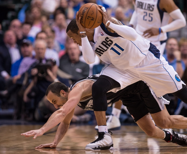 Apr 10, 2014; Dallas, TX, USA; Dallas Mavericks guard Monta Ellis (11) keeps the ball away from San Antonio Spurs guard Manu Ginobili (20) during the second half at the American Airlines Center. The Spurs defeated the Mavericks 109-100. Mandatory Credit: Jerome Miron-USA TODAY Sports