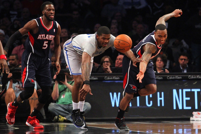 Apr 11, 2014; Brooklyn, NY, USA; Brooklyn Nets shooting guard Joe Johnson (7) and Atlanta Hawks point guard Jeff Teague (0) chase a loose ball during the first quarter of a game at Barclays Center. Mandatory Credit: Brad Penner-USA TODAY Sports