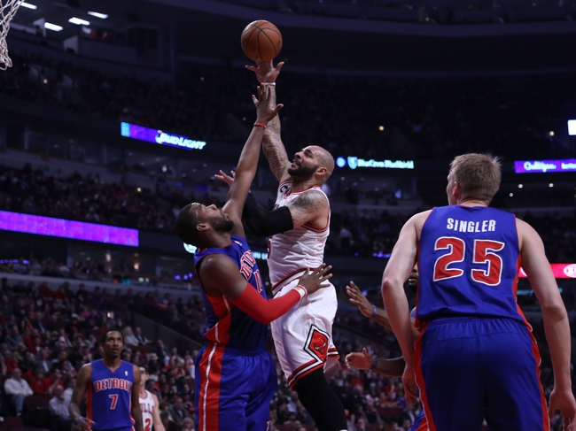 Apr 11, 2014; Chicago, IL, USA; Chicago Bulls forward Carlos Boozer (5) scores over Detroit Pistons forward Greg Monroe (10) during the first quarter at the United Center. Mandatory Credit: Dennis Wierzbicki-USA TODAY Sports