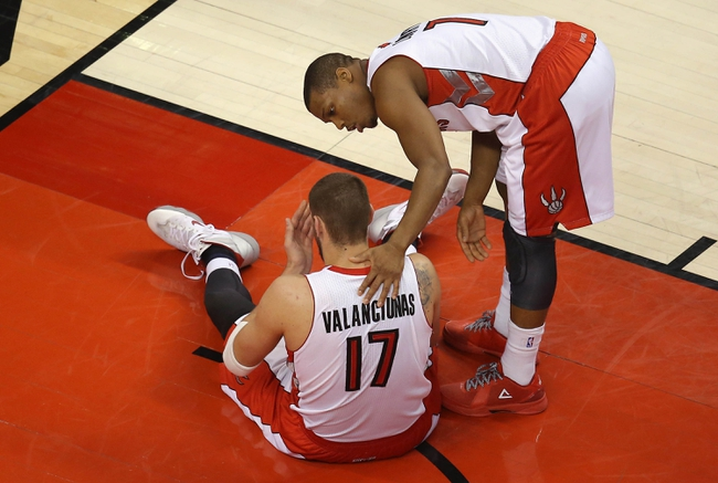 Apr 11, 2014; Toronto, Ontario, CAN; Toronto Raptors center Jonas Valanciunas (17) is tended to by point guard Kyle Lowry (7) after being fouled against the New York Knicks at Air Canada Centre. Mandatory Credit: Tom Szczerbowski-USA TODAY Sports