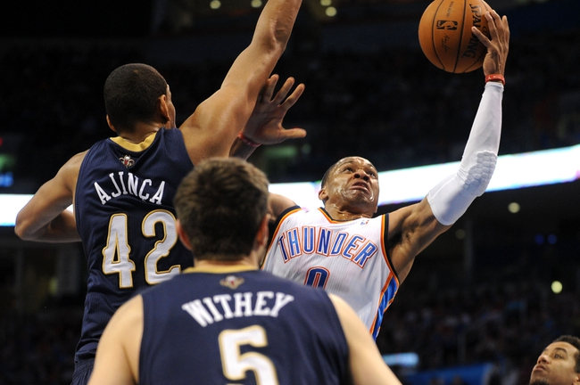 Apr 11, 2014; Oklahoma City, OK, USA;  Oklahoma City Thunder guard Russell Westbrook (0) attempts a shot against New Orleans Pelicans center Alexis Ajinca (42) during the second quarter at Chesapeake Energy Arena. Mandatory Credit: Mark D. Smith-USA TODAY Sports