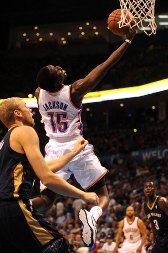 Apr 11, 2014; Oklahoma City, OK, USA; Oklahoma City Thunder guard Reggie Jackson (15) attempts a reverse layup against New Orleans Pelicans center Jeff Withey (5) during the second quarter  at Chesapeake Energy Arena. Mandatory Credit: Mark D. Smith-USA TODAY Sports