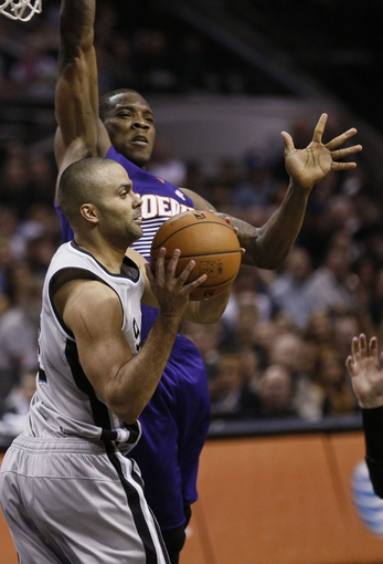 Apr 11, 2014; San Antonio, TX, USA; San Antonio Spurs guard Tony Parker (front) passes the ball under the basket against Phoenix Suns  guard Eric Bledsoe (behind) during the first half at AT&T Center. Mandatory Credit: Soobum Im-USA TODAY Sports