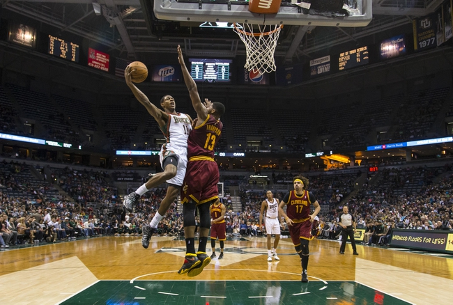 Apr 11, 2014; Milwaukee, WI, USA; Milwaukee Bucks guard Brandon Knight (11) drives for a shot as Cleveland Cavaliers forward Tristan Thompson (13) defends during the second quarter at BMO Harris Bradley Center. Mandatory Credit: Jeff Hanisch-USA TODAY Sports