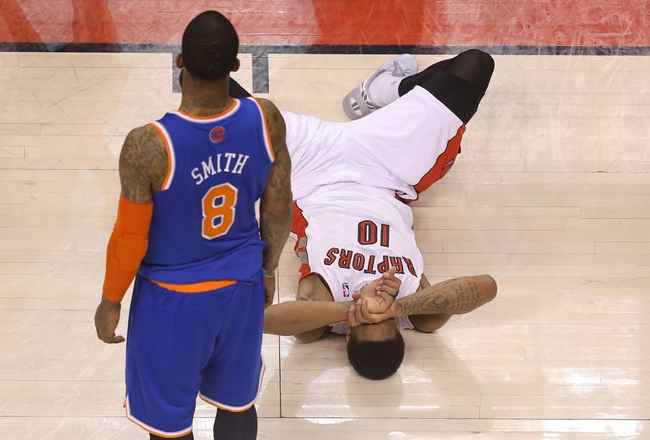 Apr 11, 2014; Toronto, Ontario, CAN; Toronto Raptors guard DeMar DeRozan (10) lays on the court after going down as New York Knicks forward J.R. Smith (8) looks on at Air Canada Centre. The Knicks beat the Raptors 108-100. Mandatory Credit: Tom Szczerbowski-USA TODAY Sports