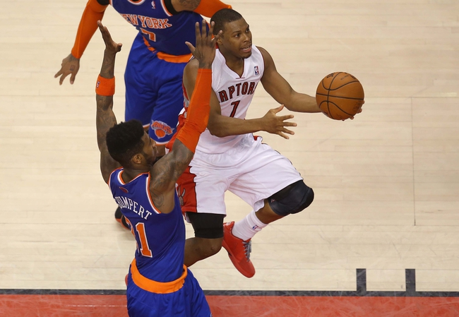 Apr 11, 2014; Toronto, Ontario, CAN; Toronto Raptors point guard Kyle Lowry (7) scores and is fouled on the play against the New York Knicks at Air Canada Centre. The Knicks beat the Raptors 108-100. Mandatory Credit: Tom Szczerbowski-USA TODAY Sports