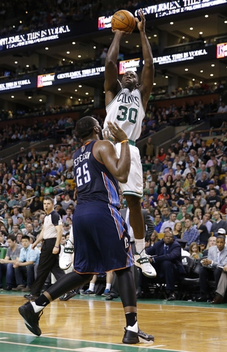 Apr 11, 2014; Boston, MA, USA; Boston Celtics forward Brandon Bass (30) shoots against Charlotte Bobcats center Al Jefferson (25) in the second half at TD Garden. The Celtics defeated the Bobcats 106-103. Mandatory Credit: David Butler II-USA TODAY Sports