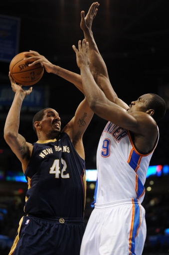 Apr 11, 2014; Oklahoma City, OK, USA;  New Orleans Pelicans center Alexis Ajinca (42) attempts a shot against Oklahoma City Thunder forward Serge Ibaka (9) during the third quarter at Chesapeake Energy Arena. Mandatory Credit: Mark D. Smith-USA TODAY Sports
