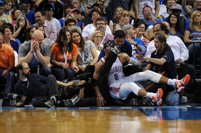 Apr 11, 2014; Oklahoma City, OK, USA;  Oklahoma City Thunder guard Russell Westbrook (0) falls into the fan seating in action against the New Orleans Pelicans during the third quarter at Chesapeake Energy Arena. Mandatory Credit: Mark D. Smith-USA TODAY Sports