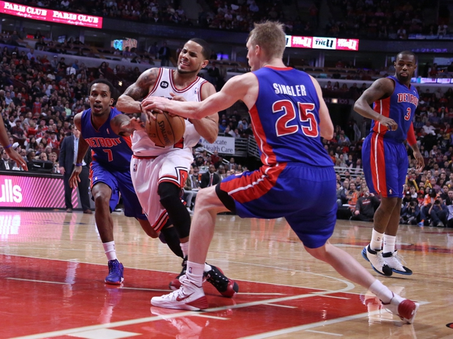 Apr 11, 2014; Chicago, IL, USA; Chicago Bulls guard D.J. Augustin (center) drives between Detroit Pistons guard Brandon Jennings (left) and forward Kyle Singler (right) during the second half at the United Center. Chicago won 106-98. Mandatory Credit: Dennis Wierzbicki-USA TODAY Sports