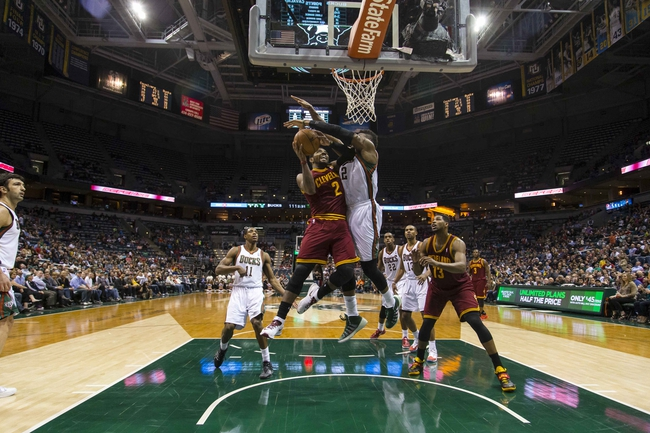 Apr 11, 2014; Milwaukee, WI, USA; Cleveland Cavaliers guard Kyrie Irving (2) shoots as Milwaukee Bucks forward Jeff Adrien (12) defends during the fourth quarter at BMO Harris Bradley Center.  Milwaukee won 119-116.  Mandatory Credit: Jeff Hanisch-USA TODAY Sports