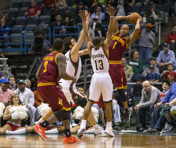 Apr 11, 2014; Milwaukee, WI, USA; Cleveland Cavaliers guard Jarrett Jack (1) passes the ball as Milwaukee Bucks center Zaza Pachulia (27) and guard Ramon Sessions (13) defend during the fourth quarter at BMO Harris Bradley Center.  Milwaukee won 119-116.  Mandatory Credit: Jeff Hanisch-USA TODAY Sports