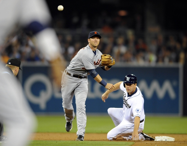 Apr 11, 2014; San Diego, CA, USA; Detroit Tigers shortstop Andrew Romine (27) turns a double play ahead of the slide by San Diego Padres left fielder Seth Smith (12) to end the third inning at Petco Park. Mandatory Credit: Christopher Hanewinckel-USA TODAY Sports