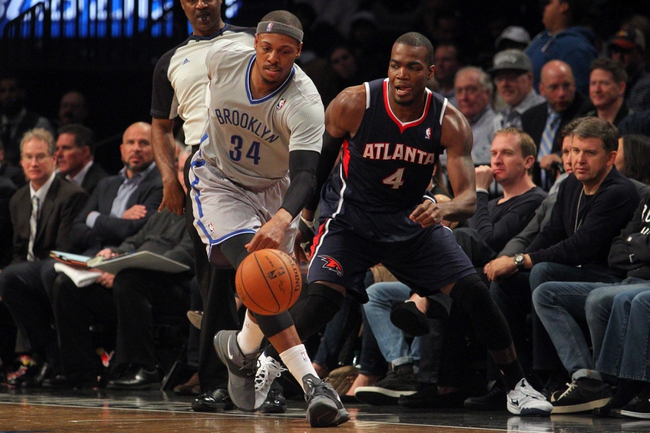 Apr 11, 2014; Brooklyn, NY, USA; Brooklyn Nets small forward Paul Pierce (34) chases a loose ball with Atlanta Hawks power forward Paul Millsap (4) during the second quarter of a game at Barclays Center. Mandatory Credit: Brad Penner-USA TODAY Sports