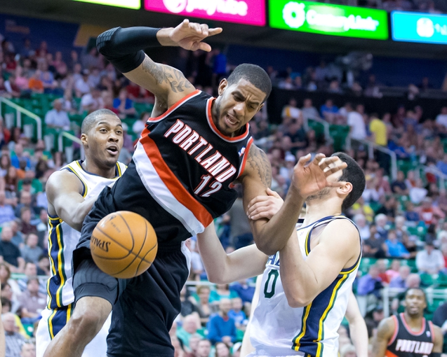 Apr 11, 2014; Salt Lake City, UT, USA; Utah Jazz center Enes Kanter (0) fouls Portland Trail Blazers forward LaMarcus Aldridge (12) during the second half at EnergySolutions Arena. Portland won 111-99. Mandatory Credit: Russ Isabella-USA TODAY Sports