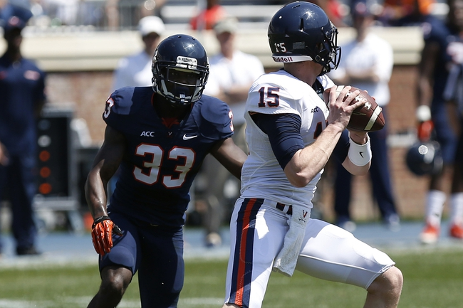 Apr 12, 2014; Charlottesville, VA, USA; Virginia Cavaliers quarterback Matt Johns (15) prepares to throw the ball as Cavaliers cornerback Kirk Garner (33) chases during the Cavaliers Spring Game at Scott Stadium. Mandatory Credit: Geoff Burke-USA TODAY Sports
