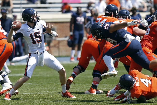 Apr 12, 2014; Charlottesville, VA, USA; Virginia Cavaliers quarterback Matt Johns (15) throws the ball as Cavaliers linebacker D.J. Hill (29) chases during the Cavaliers Spring Game at Scott Stadium. Mandatory Credit: Geoff Burke-USA TODAY Sports