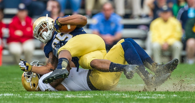 Apr 12, 2014; Notre Dame, IN, USA; Notre Dame Fighting Irish running back Tarean Folston (25) is tackled by linebacker Jaylon Smith (9) in the first quarter of the Blue-Gold Game at Notre Dame Stadium. Mandatory Credit: Matt Cashore-USA TODAY Sports