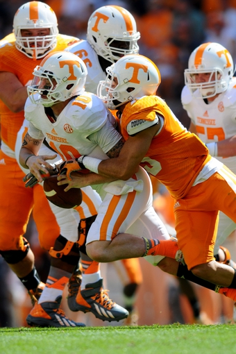 Apr 12, 2014; Knoxville, TN, USA; Tennessee Volunteers quarterback Riley Ferguson (10) is sacked by defensive back Devaun Swafford (13) during the orange and white spring game at Neyland Stadium. Mandatory Credit: Randy Sartin-USA TODAY Sports