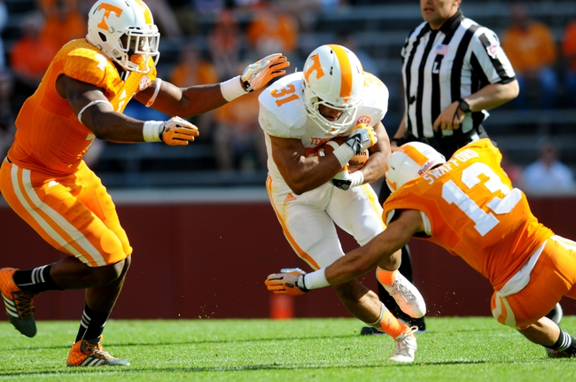 Apr 12, 2014; Knoxville, TN, USA; Tennessee Volunteers running back Justus Pickett (31) is tackled by defensive back Devaun Swafford (13) during the spring game at Neyland Stadium. Mandatory Credit: Randy Sartin-USA TODAY Sports