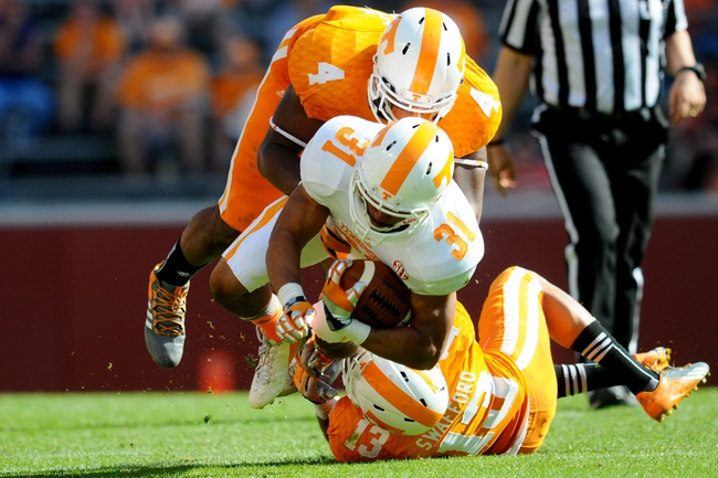 Apr 12, 2014; Knoxville, TN, USA; Tennessee Volunteers running back Justus Pickett (31) is tackled by defensive back Devaun Swafford (13) and defensive lineman LaTroy Lewis (4) during the spring game at Neyland Stadium. Mandatory Credit: Randy Sartin-USA TODAY Sports