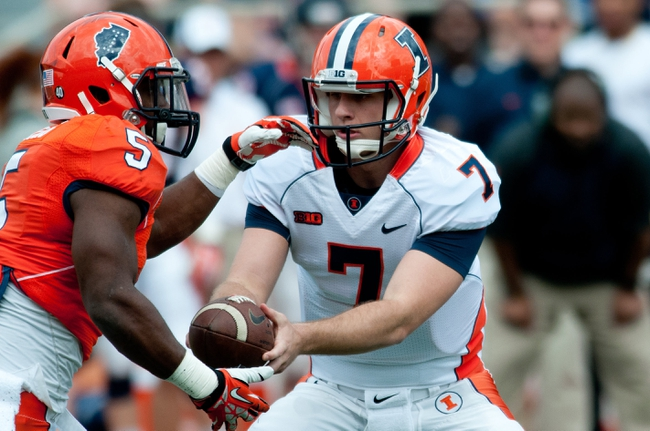 Apr 12, 2014; Champaign, IL, USA; Illinois Fighting Illini quarterback Chayce Crouch (7) hands the ball off to running back Donovonn Young (5) during the second quarter of the spring game at Memorial Stadium. Mandatory Credit: Bradley Leeb-USA TODAY Sports